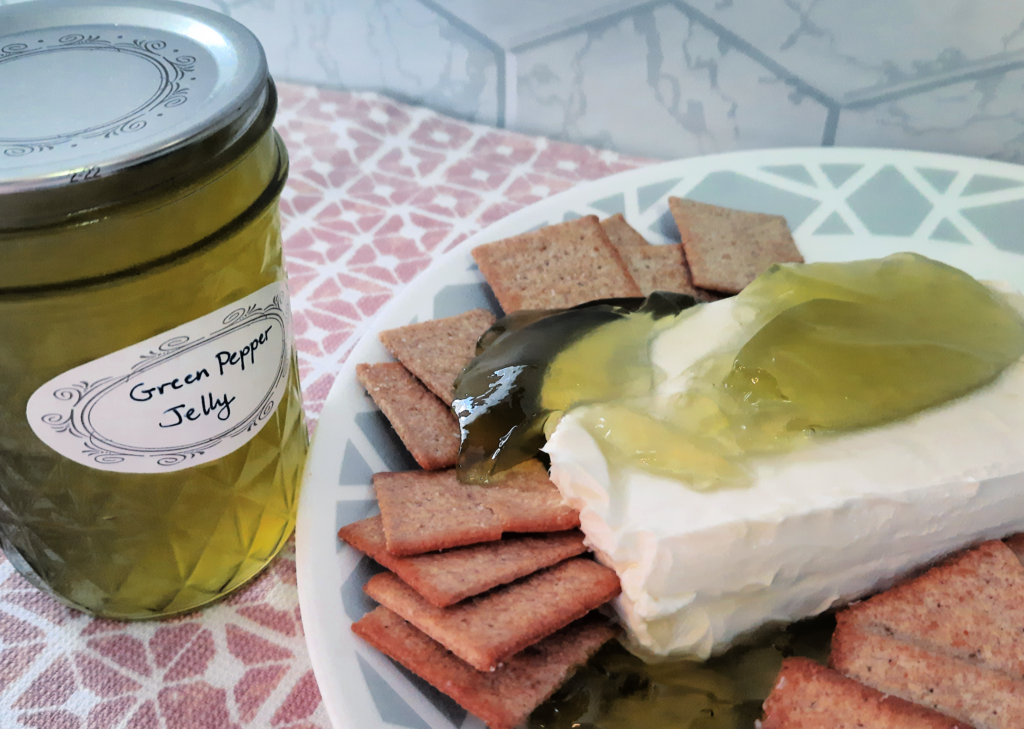 Green Pepper Jelly Jar with Green pepper jelly on cream cheese on a plate with crackers