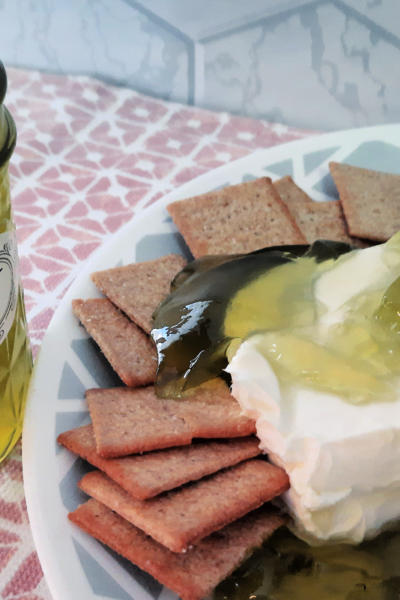 green pepper jelly jar with jelly on cream cheese with crackers on plate