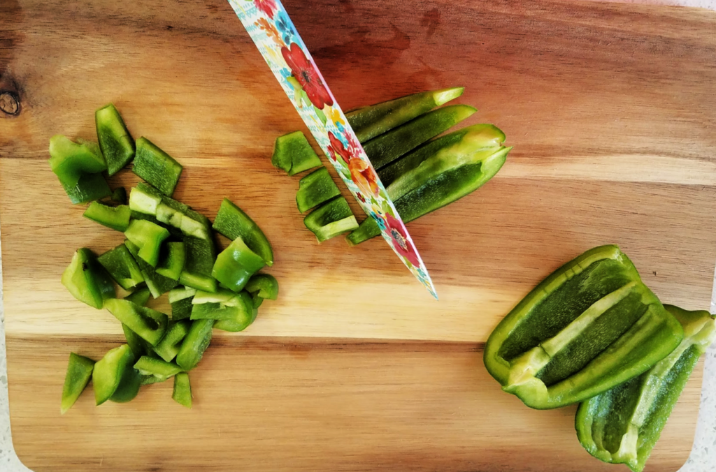Green pepper being chopped with knife on cutting board