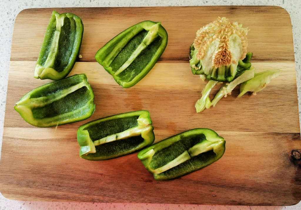 Green pepper on cutting board sliced large with seed core set to the side