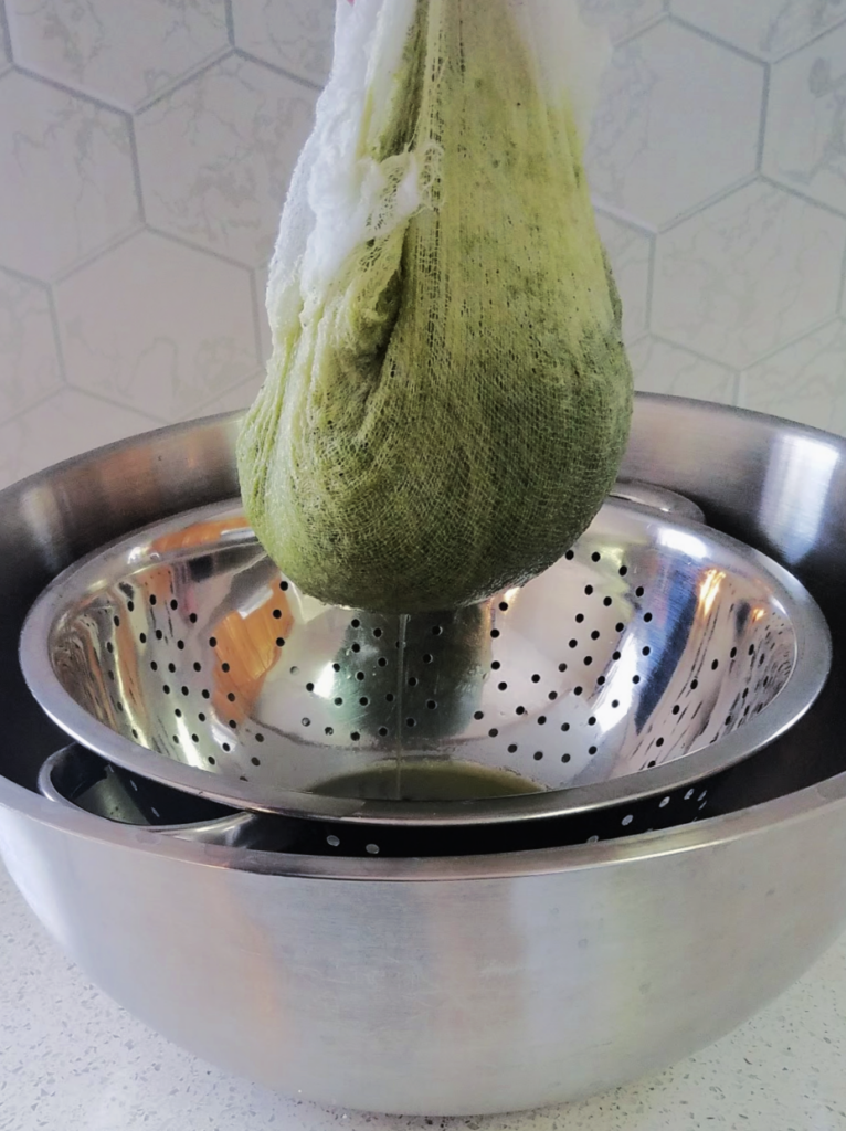 green pepper puree draining in cheesecloth into colander in bowl