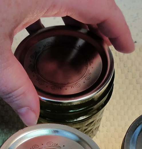 hand putting lid on canning jar