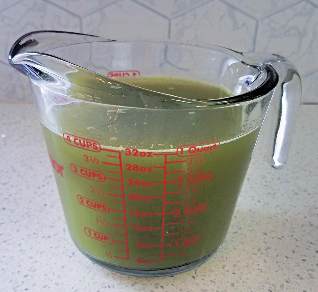 green pepper juice in liquid measuring cup