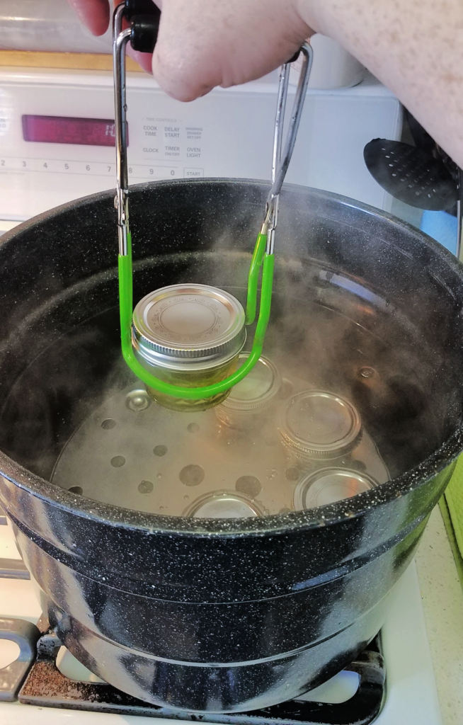hand using jar lifter to place jars into water bath canner