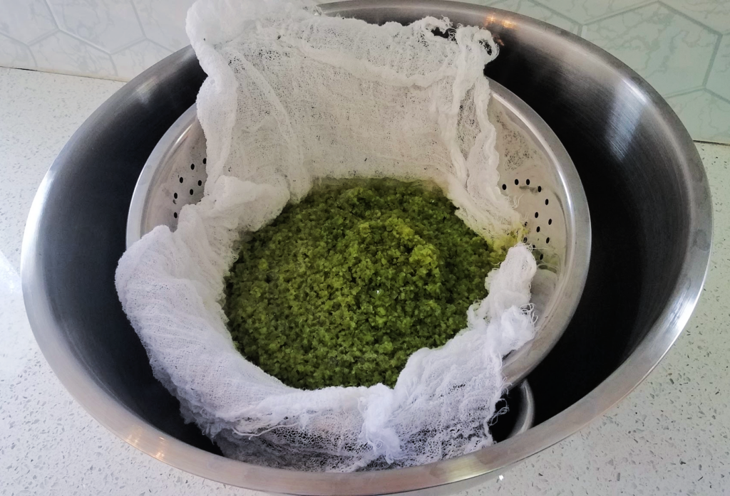 pureed green pepper mixture in cheesecloth on colander in a bowl