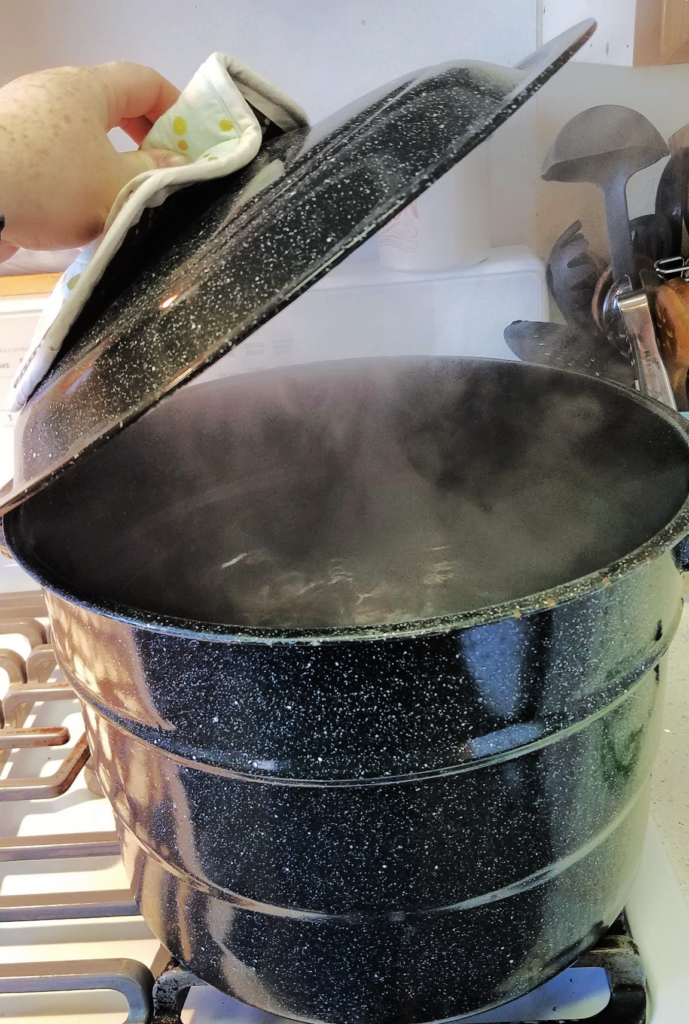 Hand removing lid from boiling water bath canner on stove