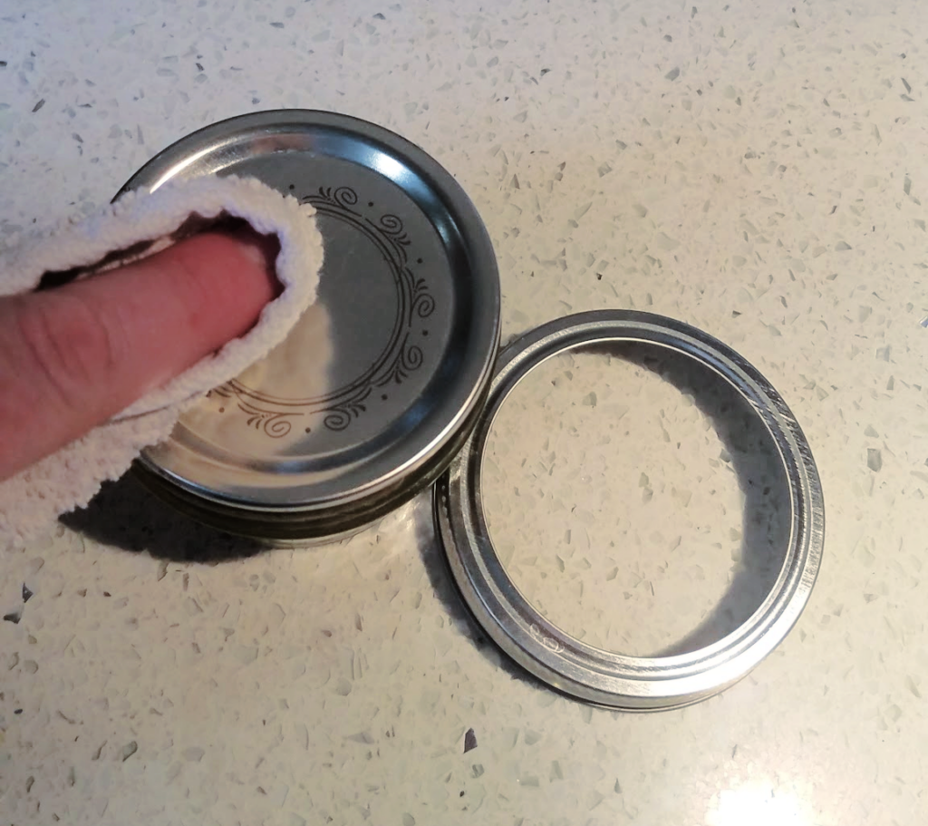 finger using paper towel to wipe off canning lid next to canning ring