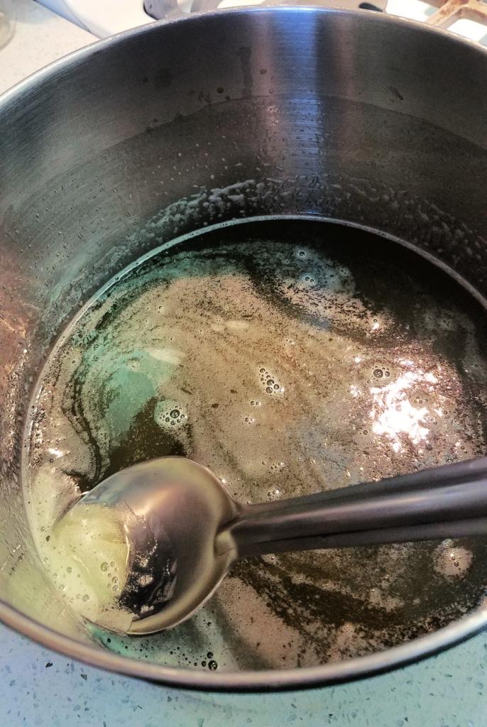 skimming foam off of green pepper jelly in a pot